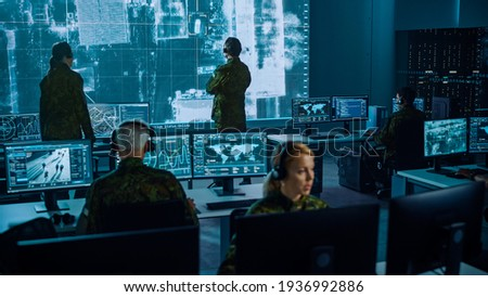 Military Surveillance Team of Officers Locked a Target on a Vehicle from a Satellite and Monitor it on a Big Display in Office for Cyber Operations for Managing Security and Army Communications. Royalty-Free Stock Photo #1936992886