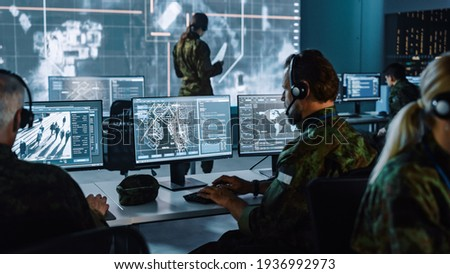 Military Surveillance Officer Working on a City Tracking Operation in a Central Office Hub for Cyber Control and Monitoring for Managing National Security, Technology and Army Communications. Royalty-Free Stock Photo #1936992973