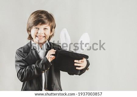 Adorable child dressed as an illusionist getting bunny from a hat over grey background Royalty-Free Stock Photo #1937003857