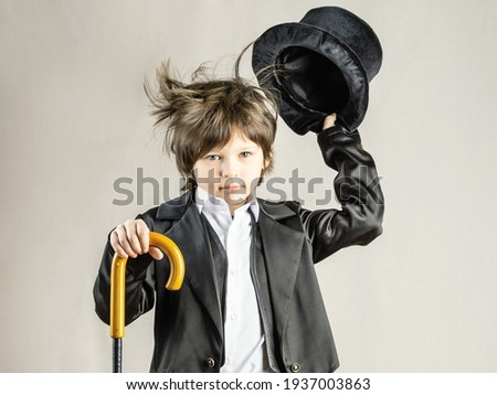 Young six year old boy wearing black suit expressively taking off his top hat. Retro party costume, Illusionist performance Royalty-Free Stock Photo #1937003863