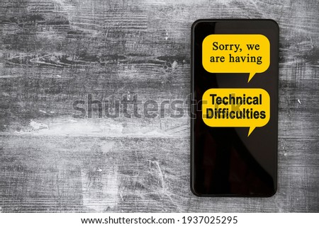 Sorry we are having Technical Difficulties message on a black mobile phone Royalty-Free Stock Photo #1937025295