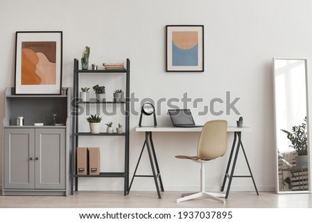 Background of minimal home office workplace in modern apartment decorated by plants and abstract art, copy space Royalty-Free Stock Photo #1937037895