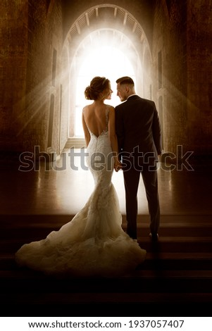 Wedding Couple in Love Back View walking down Aisle Church. Newly Wedded Bride Groom in Window Door Light. Wedding Day Ceremony Royalty-Free Stock Photo #1937057407