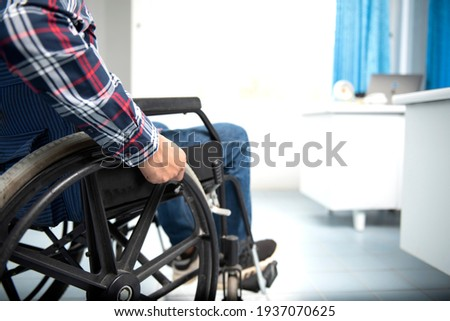 A disabled man on a wheelchair in the office Young man with disabilities in Asia. A man on a wheelchair Recovery and health care ideas Teamwork in Office Royalty-Free Stock Photo #1937070625
