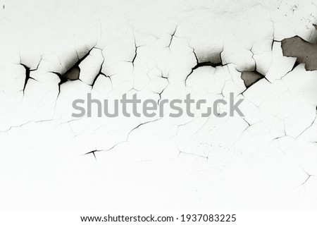 Old white paint on wall. Surface texture with cracked peeling paint. Close-up background. Royalty-Free Stock Photo #1937083225