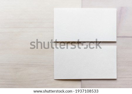 Mockup template with two blank business cards on wooden background.