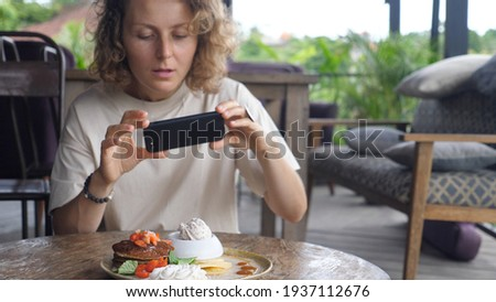 Sharing photos of lunch on social media.Female food blogger taking picture of her healthy and delicious vegan pancakes