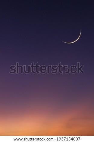 Islamic Moon sky on Dark Blue Dusk Vertical,Twilight Sky in the Evening with Sunset and Beautiful Sunlight and Crescent moon, symbol of religion islamic begin Ramadan month, Eid al-Adha, Eid al fitr Royalty-Free Stock Photo #1937154007