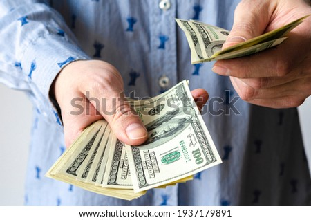 A bundle of American dollars money is rolled up in a hand. Money tied with an elastic band. Roll of American dollars. Human hand. Business and finance. Currency and finance. Cash business. Royalty-Free Stock Photo #1937179891
