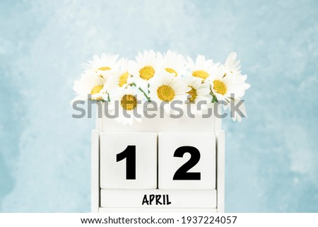 White cube calendar for April with daisy flowers over blue background with copy space Royalty-Free Stock Photo #1937224057