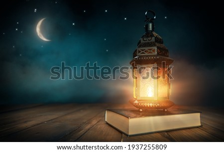 Ornamental Arabic lantern with burning candle glowing at night. Festive greeting card, invitation for Muslim holy month Ramadan Kareem. Royalty-Free Stock Photo #1937255809