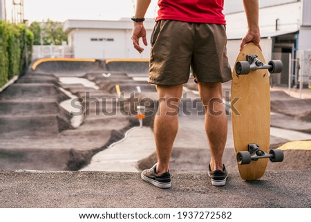 Closeup Asian man holding surfskate or skate board in pumptrack skate Park when sunrise time over photo blur of pumptrack curve, extream sport, healthy and exercise, fashion in covid19 concept
