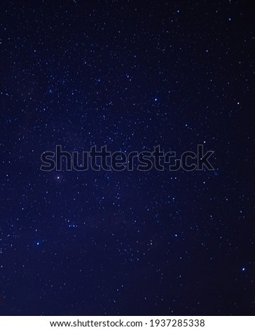 Background image of starry night sky. Image contains noise and grains due to high ISO and soft focus due to slow shutter. Royalty-Free Stock Photo #1937285338