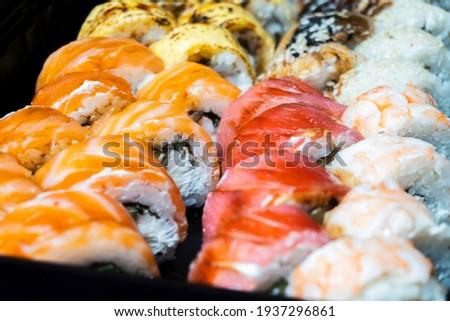 Sushi rolls with shrimp, avocado, eel, chedar cheese, sesame seeds, caviar, tuna, nori, cucumber and cream cheese close-up, selective focus