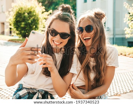 Portrait of two young beautiful smiling hipster women in trendy summer white t-shirt clothes.Sexy carefree women posing on street background. Positive models having fun, hugging and taking selfie Royalty-Free Stock Photo #1937340523