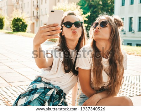 Portrait of two young beautiful smiling hipster women in trendy summer white t-shirt clothes.Sexy carefree women posing on street background. Positive models having fun, hugging and taking selfie Royalty-Free Stock Photo #1937340526