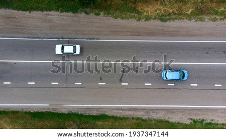 Aerial. Two sedan cars driving by the highway. Top view from drone.  Royalty-Free Stock Photo #1937347144