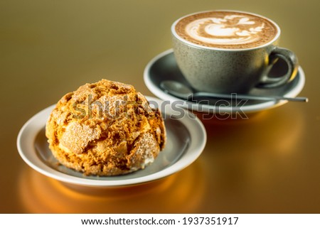 Sweet and crispy brioche bread served with a delicious cappuccino Royalty-Free Stock Photo #1937351917
