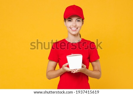 Delivery employee woman in red cap blank t-shirt work courier in service during quarantine coronavirus covid-19 virus holding Chinese food takeaway carton container box isolated on yellow background
