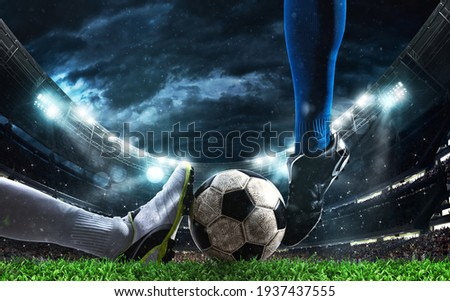Close up of a football action scene with competing soccer players at the stadium Royalty-Free Stock Photo #1937437555