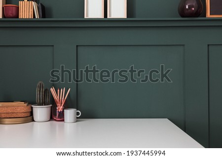 Home office desk in the corner, office supplies, mug with tools, notes, books and dark green wall. Homeschooling concept. Trendy, creative workspace. Royalty-Free Stock Photo #1937445994