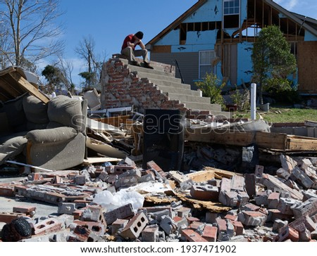 Man sitting on steps after a major tornado destroyed his home Royalty-Free Stock Photo #1937471902