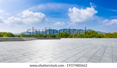 Wide city square and green mountain in summer.