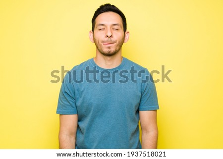 Cheerful man thinking about eating a delicious lunch with his eyes closed. Handsome man in his 30s licking his lips and craving a tasty dinner Royalty-Free Stock Photo #1937518021