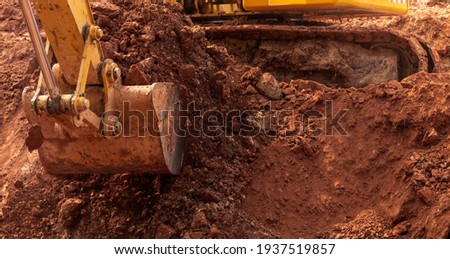 Blur photo of backhoe working by digging soil at construction site. Bucket of backhoe digging soil. Crawler excavator digging on dirt. Excavating machine. Earth moving machine. Excavation vehicle.