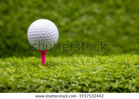 Golf ball is on pink tee on green grass background Royalty-Free Stock Photo #1937532442
