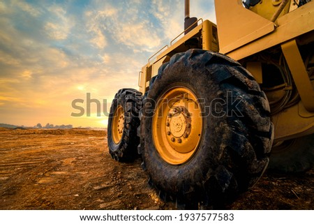 Big rubber wheels of soil grade tractor car earthmoving at road construction side. Close-up of a dirty loader wheel with a large tread with sky sunset Royalty-Free Stock Photo #1937577583