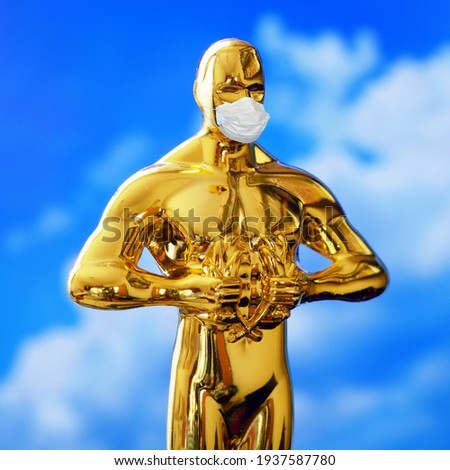Hollywood Golden Oscar Academy award statue in medical mask on blue sky background with copy space. Success and victory concept. Oscar ceremony in coronavirus time