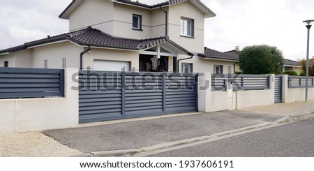 modern door gate of white two storey house driveway entrance gates home access garage in suburb Royalty-Free Stock Photo #1937606191