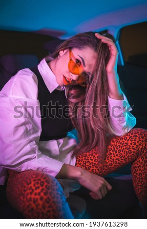 Urban photography with blue and purple neons in a car. Young blonde Caucasian model pose with hearts glasses and a white shirt