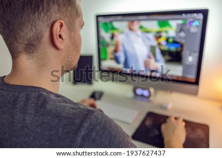 Editing photos in an application program on a desktop computer. A photo of a man from behind working on the preparation of photo and video material for a business partner. Creative work and hobby