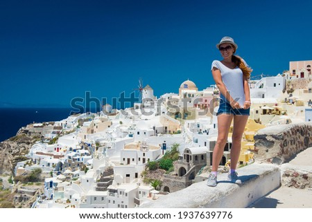 Beautiful white exterior Santorini. Architecture of island, the most romantic island in the world, Greece.  Luxury holiday at the hotel near the sea.  Travel to Greece. Girl tourist Royalty-Free Stock Photo #1937639776
