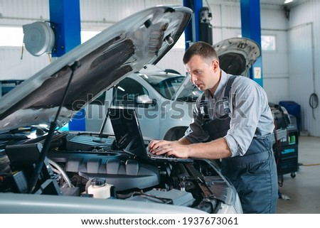 car mechanic using a computer laptop to diagnosing and checking up on car engines parts for fixing and repair Royalty-Free Stock Photo #1937673061