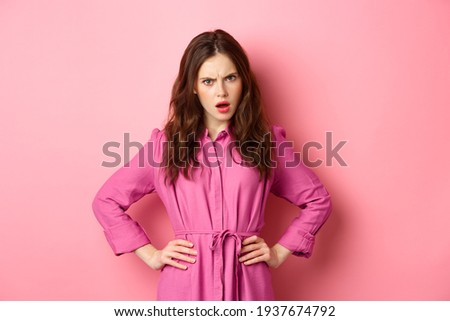 Angry and confused girlfriend staring with disappointment, look from under forehead, frowning and holding hands on waist, judging someone, condemn behaviour, standing against pink background Royalty-Free Stock Photo #1937674792