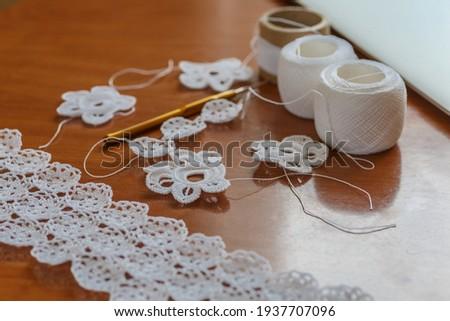 Crochet knitting. Lace of flowers.  Handmade Irish lace as a background Royalty-Free Stock Photo #1937707096
