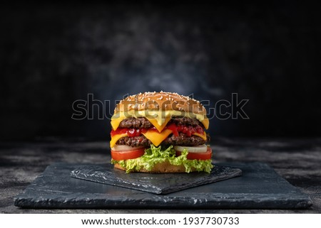 Fresh tasty burger on dark background Royalty-Free Stock Photo #1937730733