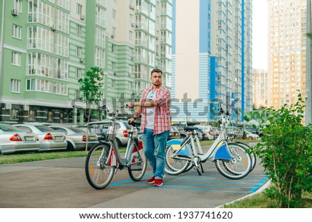 Adult man with a beard walks with a rented city bike against the backdrop of the cityscape. Man in casual clothes picked up a bicycle from a row of bicycles. A walk on a bicycle