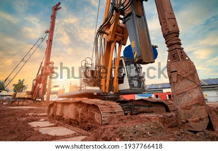 Hydraulic pile drilling machine worker digging at industrial construction site. Hydraulic Drilling Rig. Device of bored pile with casing. Foundation and ground. Drilling in the ground. Technologies. Royalty-Free Stock Photo #1937766418