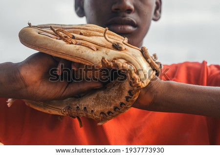 boy with brown skin and latin origin playing baseball in the park with ball, glove and bat, dark Dominican boy with baseball uniform and cap Royalty-Free Stock Photo #1937773930