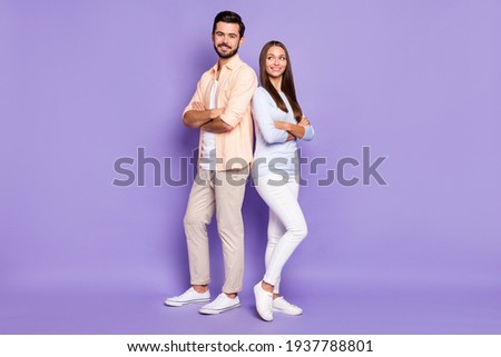 Full size portrait of two cheerful persons standing back to back folded arms isolated on purple color background