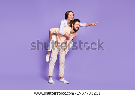 Full size photo of happy young couple man piggyback woman point finger empty space isolated on purple color background