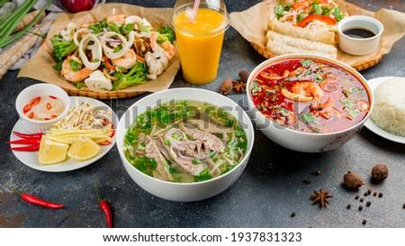 Assorted asian dinner, vietnamese food. Pho bo, pho tom, noodles, spring rolls, tom yam, rice, mango shake on beautiful black stone table Royalty-Free Stock Photo #1937831323