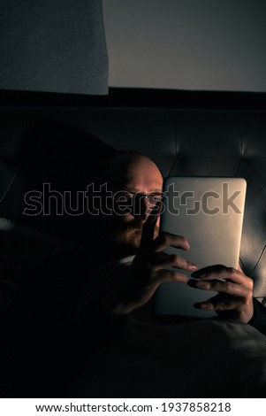 Young bearded male on a tablet in bed. Nightlife. Relaxing. Social media.