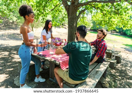 Multiracial young people drinking red wine at park sunny day. Multiethnic friends having fun a picnic. Interracial person hanging out and relaxing. Serenity and tranquility and feel good concept.