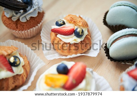 Close-up picture of baked cupcakes with cream cheese icing and fruits on top, mint macarons. Colorful sweet pastries on wooden table buffet. Festive holiday celebration. party. Fancy mini desserts.