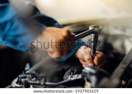 Caucasian male mechanic repairs car in garage. Car maintenance and auto service garage concept. Close up mechanical hand and spanner. Royalty-Free Stock Photo #1937901619
